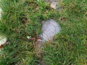 An oil tank cap in the yard likely indicates that a buried heating oil tank is located on the property.